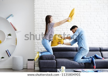 Young hispanic couple sitting on sofa at home, having fun and enjoying quality time. The girl is playing pillow fight with her boyfriend and smiles. Slow motion