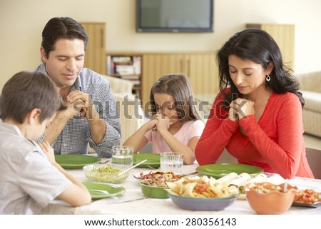 Young Hispanic Family Saying Prayers Before Meal At Home