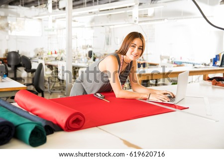 Young Hispanic fashion designer using a laptop computer in a textile factory