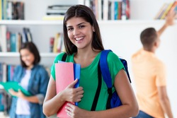 Young hispanic female student with group of young adults at classroom of university