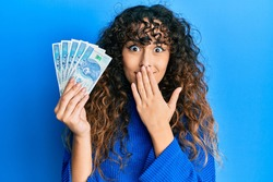 Young hispanic girl holding 50 polish zloty banknotes covering mouth with hand, shocked and afraid for mistake. surprised expression