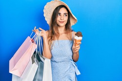 Young hispanic girl holding shopping bags and ice cream smiling looking to the side and staring away thinking.