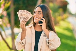 Young hispanic girl talking on the smartphone and hoding mexican pesos banknotes at the park.