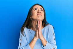 Young hispanic girl wearing casual clothes begging and praying with hands together with hope expression on face very emotional and worried. begging.