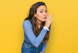 Young hispanic girl wearing casual clothes hand on mouth telling secret rumor, whispering malicious talk conversation