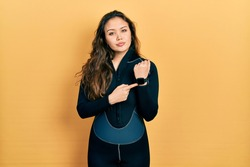 Young hispanic girl wearing diver neoprene uniform in hurry pointing to watch time, impatience, looking at the camera with relaxed expression