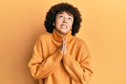 Young hispanic girl wearing wool winter sweater begging and praying with hands together with hope expression on face very emotional and worried. begging.