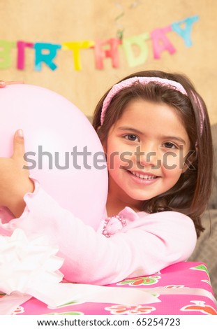 stock photo : Young Hispanic girl with large gift and balloon