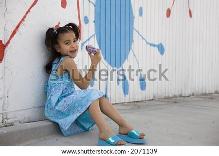 Young hispanic girl with lollipop