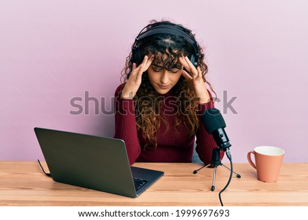 Young hispanic girl working at radio office with hand on head, headache because stress. suffering migraine.  Photo stock ©
