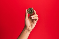 Young hispanic hand holding bitcoin over isolated red background.