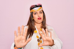 Young hispanic hippie woman wearing fashion boho style and sunglasses over pink background Moving away hands palms showing refusal and denial with afraid and disgusting expression. Stop and forbidden.