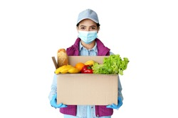 Young hispanic indian woman courier worker wears medical face mask, gloves looking at camera holding grocery food delivery box in hands concept stand isolated on white studio background. Portrait