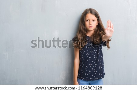 Young hispanic kid over grunge grey wall doing stop sing with palm of the hand. Warning expression with negative and serious gesture on the face. #1164809128