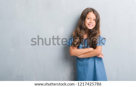 Young hispanic kid over grunge grey wall happy face smiling with crossed arms looking at the camera. Positive person. #1217425786