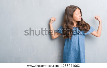 Young hispanic kid over grunge grey wall surprised with hand on head for mistake, remember error. Forgot, bad memory concept.