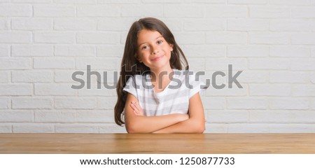 Young hispanic kid sitting on the table at home happy face smiling with crossed arms looking at the camera. Positive person.