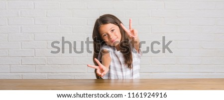 Young hispanic kid sitting on the table at home smiling looking to the camera showing fingers doing victory sign. Number two.