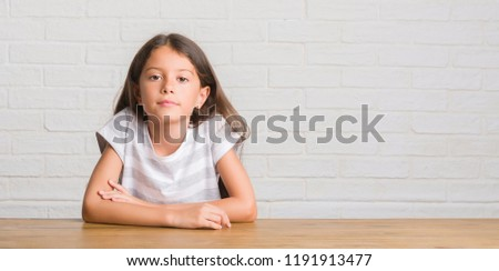 Young hispanic kid sitting on the table at home with serious expression on face. Simple and natural looking at the camera.