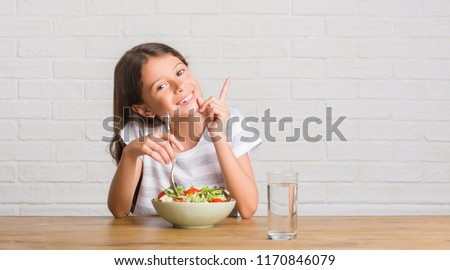 Young hispanic kid sitting on the table eating healthy salad very happy pointing with hand and finger to the side