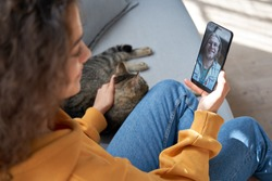 Young hispanic latin teen girl relax sit on sofa with cat at home holding phone video calling distance friend dating online on mobile screen using smartphone videochat app. Over shoulder closeup view