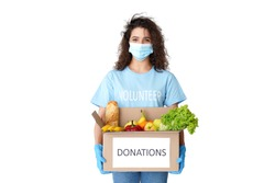 Young hispanic latin woman courier wears volunteer tshirt, medical face mask, gloves look at camera holding donations box delivering food delivery stand isolated on white studio background. Portrait.