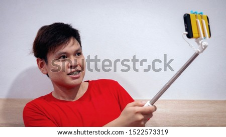Young hispanic man having fun shooting mobile phone or smart phone with selfie stick and holding stick playing with face expressing isolated on white background with copy space for text concept.