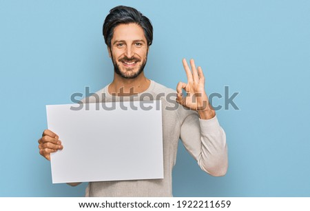 Young hispanic man holding blank empty banner doing ok sign with fingers, smiling friendly gesturing excellent symbol  Foto stock ©