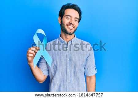 Young hispanic man holding blue ribbon looking positive and happy standing and smiling with a confident smile showing teeth