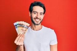 Young hispanic man holding canadian dollars looking positive and happy standing and smiling with a confident smile showing teeth