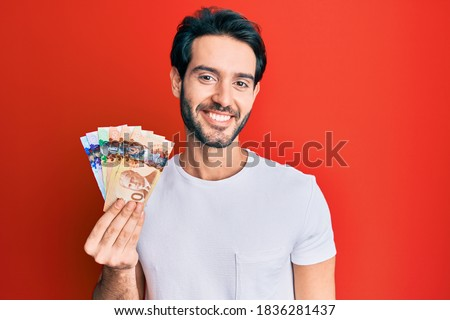 Young hispanic man holding canadian dollars looking positive and happy standing and smiling with a confident smile showing teeth  Photo stock ©