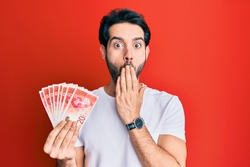 Young hispanic man holding 20 israel shekels banknotes covering mouth with hand, shocked and afraid for mistake. surprised expression