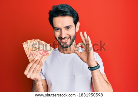Young hispanic man holding mexican pesos doing ok sign with fingers, smiling friendly gesturing excellent symbol  Foto stock ©