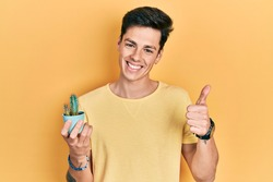 Young hispanic man holding small cactus pot smiling happy and positive, thumb up doing excellent and approval sign