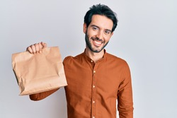 Young hispanic man holding take away food looking positive and happy standing and smiling with a confident smile showing teeth