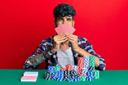 Young hispanic man playing gambling poker covering face with cards smiling and laughing hard out loud because funny crazy joke.
