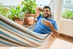 Young hispanic man relaxed drinking mug of coffee lying on the hammock at terrace.