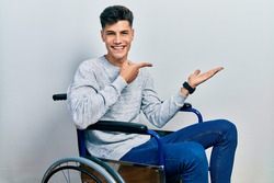 Young hispanic man sitting on wheelchair amazed and smiling to the camera while presenting with hand and pointing with finger.