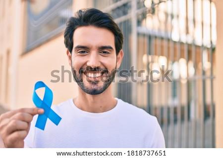 Young hispanic man smiling happy holding blue ribbon at the city. Foto stock ©