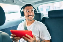 Young hispanic man smiling happy using touchpad and headphones at the car.