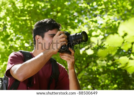 young hispanic man trekking among trees and taking pictures with dslr camera. Horizontal shape, side view, copy space