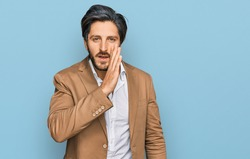 Young hispanic man wearing business clothes hand on mouth telling secret rumor, whispering malicious talk conversation