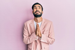 Young hispanic man wearing business jacket begging and praying with hands together with hope expression on face very emotional and worried. begging.
