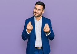Young hispanic man wearing business jacket doing money gesture with hands, asking for salary payment, millionaire business