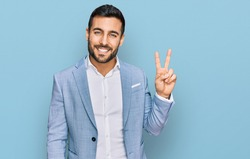 Young hispanic man wearing business jacket smiling with happy face winking at the camera doing victory sign. number two.