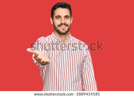 Young hispanic man wearing business shirt smiling friendly offering handshake as greeting and welcoming. successful business.  Foto stock ©