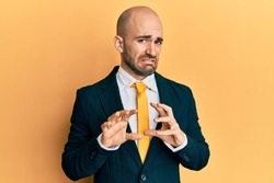 Young hispanic man wearing business suit and tie disgusted expression, displeased and fearful doing disgust face because aversion reaction. with hands raised