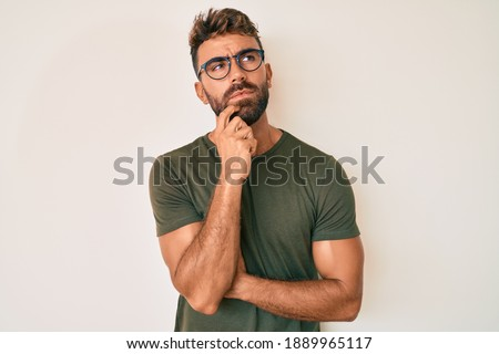 Young hispanic man wearing casual clothes and glasses serious face thinking about question with hand on chin, thoughtful about confusing idea