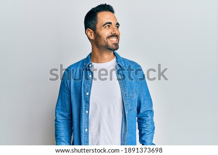 Young hispanic man wearing casual clothes looking to side, relax profile pose with natural face and confident smile.  Foto stock ©