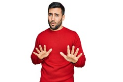 Young hispanic man wearing casual clothes moving away hands palms showing refusal and denial with afraid and disgusting expression. stop and forbidden.